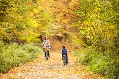 有循环在秋天公园的小儿子的母亲 库存图片