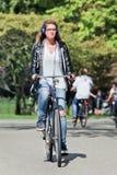 有循环在晴朗的Vondelpark,阿姆斯特丹,荷兰的耳机的女孩 库存照片