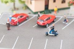 有微型人民、汽车和滑行车的拥挤的街 库存照片