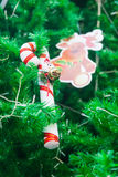 有微型圣诞老人的棒棒糖和在圣诞树的驯鹿装饰品 库存图片