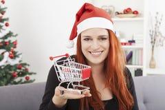 有微型购物台车推车的圣诞节女孩 免版税库存照片