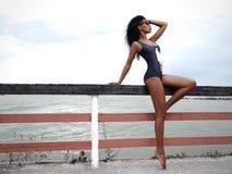 有微小的被晒黑的图的可爱的妇女在时髦游泳衣和太阳镜在路轨和水附近摆在沿海岸区 免版税库存图片