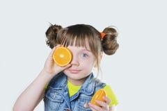 有微笑和一个桔子的女婴在手上 免版税库存照片