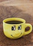 有微笑和咖啡的黄色杯子在与一立即cof的桌上 库存照片