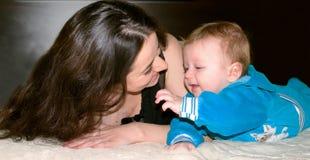 有微笑和打比赛的小婴孩的愉快的妇女 库存照片