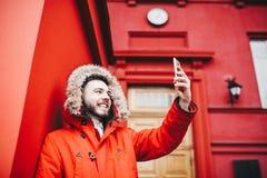 有微笑和胡子的英俊的年轻男学生在背景红色墙壁,教育机构门面上站立红色冬天ja的 库存照片