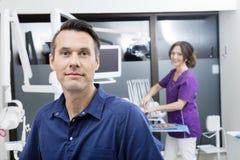 有微笑对诊所的女性助理的确信的牙医 免版税库存照片