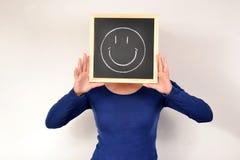 有微笑的妇女在黑板 库存照片