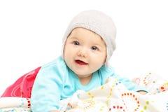 有微笑的帽子的女婴躺下和 图库摄影