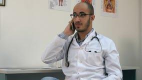 有微笑的男性的医生一次快乐的电话交谈 库存图片