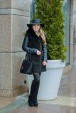 有微笑的美丽的女孩在帽子在城市附近走 免版税库存照片
