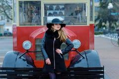 有微笑的美丽的女孩在帽子在城市附近走 库存照片