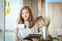 有微笑的美丽的女实业家,显示空白的名片 库存照片