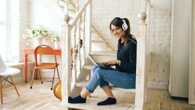 有微笑的耳机和的膝上型计算机的美丽的妇女摆在和,当在家时坐台阶 免版税库存图片