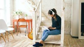 有微笑的耳机和的膝上型计算机的美丽的妇女摆在和,当在家时坐台阶 图库摄影