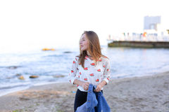 有微笑的迷人的妇女沿在战争的海岸摆在并且走 库存照片