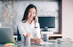 有微笑的面孔的亚裔女实业家谈话在机动性和命令 免版税库存照片
