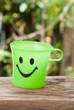 有微笑的绿色塑料杯子 免版税图库摄影