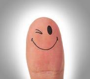 有微笑面孔的女性拇指在手指 库存照片