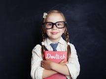 有德国书的小微笑的女孩 图库摄影