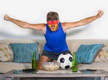 有德国旗子的年轻有吸引力的人橄榄球支持者绘了面孔在庆祝vict的电视的愉快和激动的观看的杯子比赛 免版税库存照片