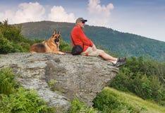 有德国牧羊犬狗的人在岩石 免版税库存图片