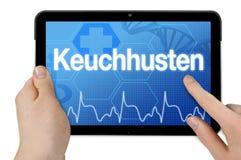 有德国词的片剂计算机百日咳的- Keuchhusten 免版税库存照片