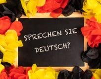 有德国颜色的黑板和德国文本sprechen sie德意志,用英语您讲德语 库存图片