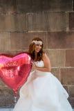 有心形一个大的气球的红头发人新娘 库存照片