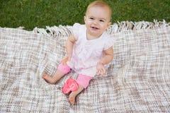 有心形的棒棒糖的逗人喜爱的婴孩坐毯子在公园 免版税库存照片