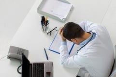 有心电图和膝上型计算机的医生在诊所 免版税库存照片