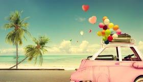 有心脏五颜六色的气球的葡萄酒桃红色经典汽车在海滩蓝天 免版税库存图片