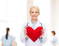 有心脏和听诊器的微笑的女性医生 免版税图库摄影