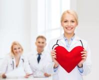 有心脏和听诊器的微笑的女性医生 库存照片