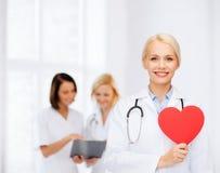 有心脏和听诊器的微笑的女性医生 免版税库存照片