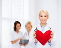 有心脏和听诊器的微笑的女性医生 图库摄影