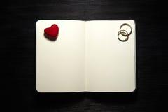 有心脏和婚戒的空白的笔记本在黑背景 免版税库存照片