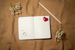 有心脏和婚戒的空白的笔记本 免版税库存图片