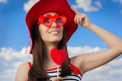 有心脏太阳镜和,棒棒糖和一个草帽的美丽的女孩在蓝天 免版税库存照片