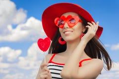 有心脏太阳镜和,棒棒糖和一个草帽的美丽的女孩在蓝天 库存照片