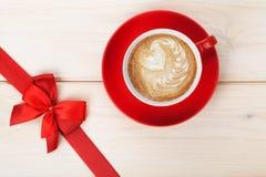 有心脏形状和红色弓的咖啡杯 免版税图库摄影