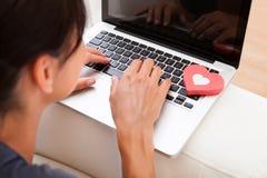 有心脏形状和膝上型计算机的妇女 库存照片