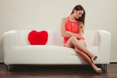 有心脏形状枕头的哀伤的妇女 红色上升了 免版税库存图片