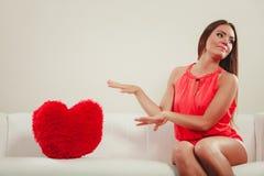 有心脏形状枕头的哀伤的妇女 红色上升了 免版税图库摄影