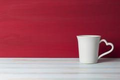 有心脏把柄的白色杯子在前面红色难看的东西背景中 库存照片