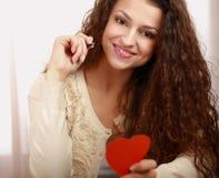 有心脏标志的美丽的微笑的妇女 库存图片
