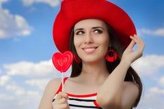 有心脏棒棒糖和草帽的美丽的女孩在蓝天 库存图片