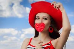 有心脏棒棒糖和草帽的美丽的女孩在蓝天 免版税库存照片