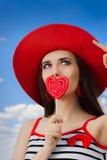 有心脏棒棒糖和草帽的美丽的女孩在蓝天 免版税库存图片