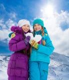 有心脏的两个女孩由雪制成 免版税图库摄影